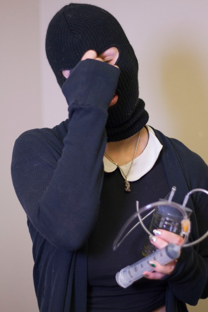 Because of the illegal nature of her work, Jane wears a ski mask to protect her identity. She is holding a menstrual extraction kit, which she makes using commonly found supplies. (Photo by Jose Olivares)